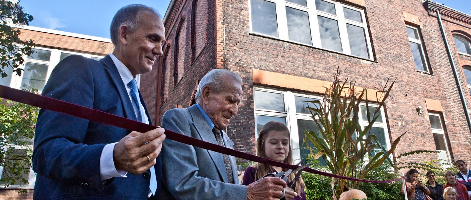 Alexander Zeeb, Walter Littek und Daria Gerter zerschneiden die Banderole zur Einweihung des Gebäudes. ©Martens